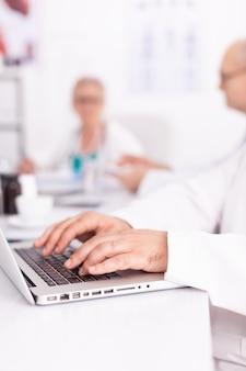 Close-up van doktershanden die op het toetsenbord van de laptop typen tijdens een ontmoeting met zijn medisch team. kliniekdeskundige therapeut in gesprek met collega's over ziekte, medisch professional