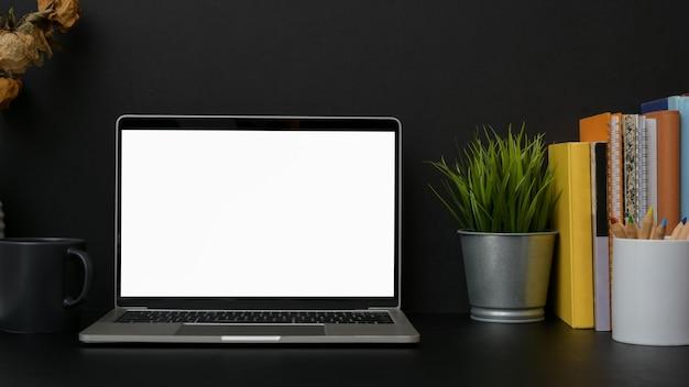 Close-up van donkere moderne werkplek met leeg scherm laptop met donkere muur