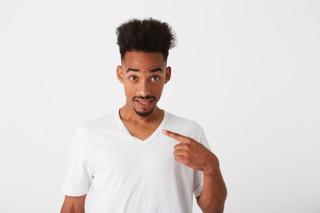 Close-up van doordachte aantrekkelijke jonge man met krullend haar en sproeten draagt t-shirt kijkt nadenkend en denken geïsoleerd over witte muur kijkt naar de zijkant