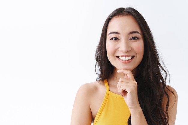 Close-up van doordachte en gelukkige jonge intelligente oost-aziatische vrouwelijke ondernemer die nieuwe concepten voor haar bedrijf bedenkt, kin peinzend en glimlachend aanraakt, goed idee hoort, plan goedkeurt