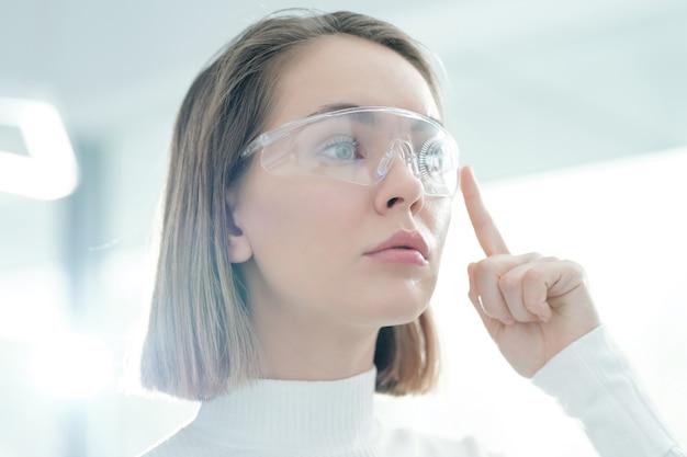 Close-up van doordachte jonge vrouw setups op slimme bril in kantoor kiezen