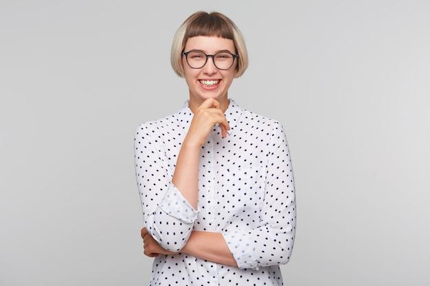 Close-up van doordachte mooie blonde jonge vrouw draagt polka dot shirt