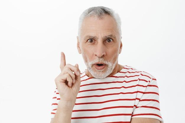 Close-up van doordachte senior man wijsvinger verhogen, hebben suggestie