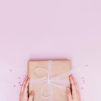 Close-up van doos van de de holdings de verjaardag verpakte gift van de hand met wit lint op roze achtergrond
