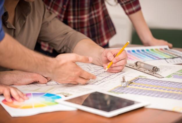 Close-up van drie jonge creatieve ontwerpers werken.