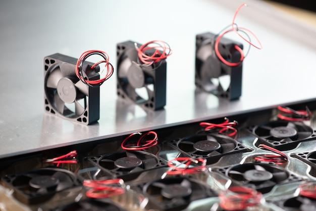Close-up van drie kleine computerkoelers met draden die op een lijst op grijs liggen