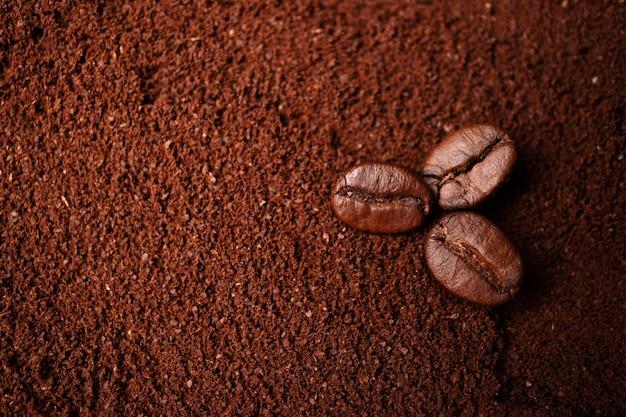 Close-up van drie koffiebonen bij de gemengde hoop gebrande koffie