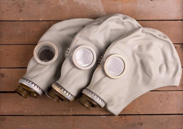 Close-up van drie oude gasmaskers op houten kist
