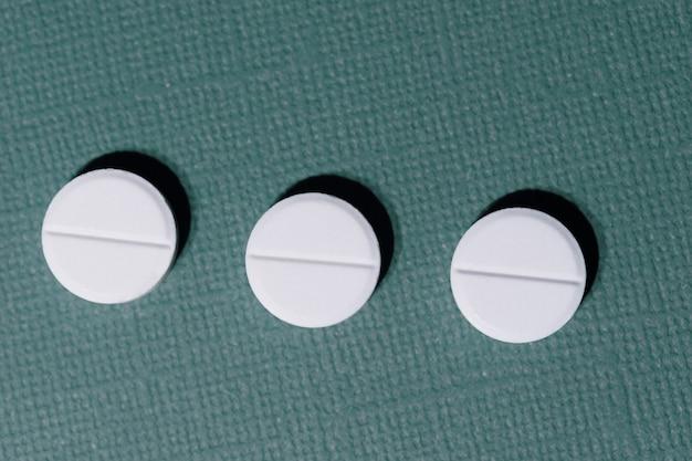 Close-up van drie tabletten op een donkergroene achtergrond