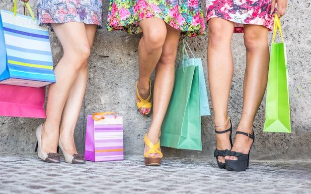 Close up van drie vrouwen met boodschappentassen, uitzicht op de vloer met hoge hakken en boodschappentassen
