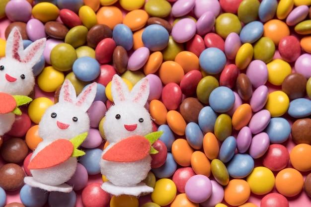 Close-up van drie witte konijntjes over het kleurrijke gemsuikergoed