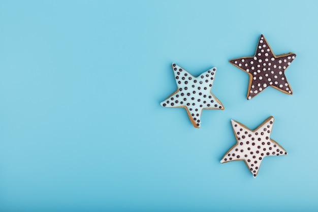 Close-up van drie zelfgemaakte geglazuurde peperkoek cookies gemaakt in de vorm van sterren. handgemaakte koekjes. vrije ruimte.