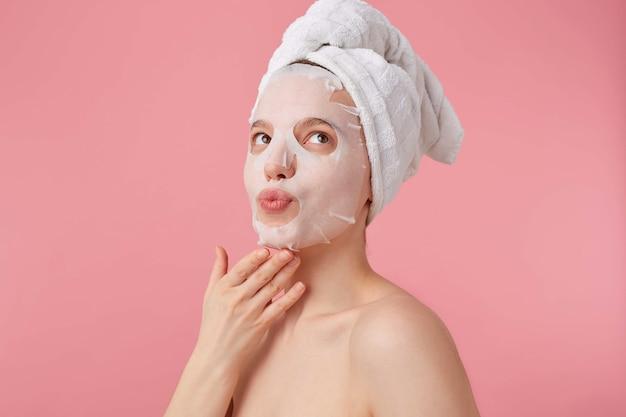 Close up van dromen jonge vrouw met een handdoek op haar hoofd na het douchen, opgezocht en na te denken over nieuwe lippenstift, stands.