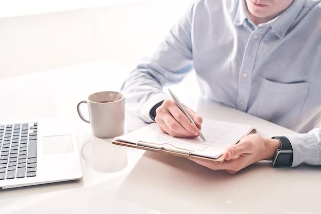 Close-up van drukke man teruggekeerd van buitenlandse reizen aan tafel zitten en formulier invullen