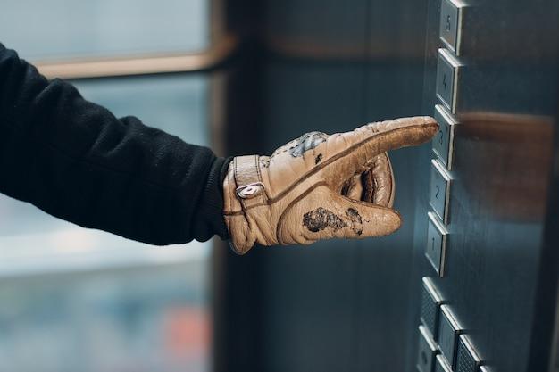 Close-up van duimen omhoog door op de knoplift te drukken tijdens coronavirus pandemie covid