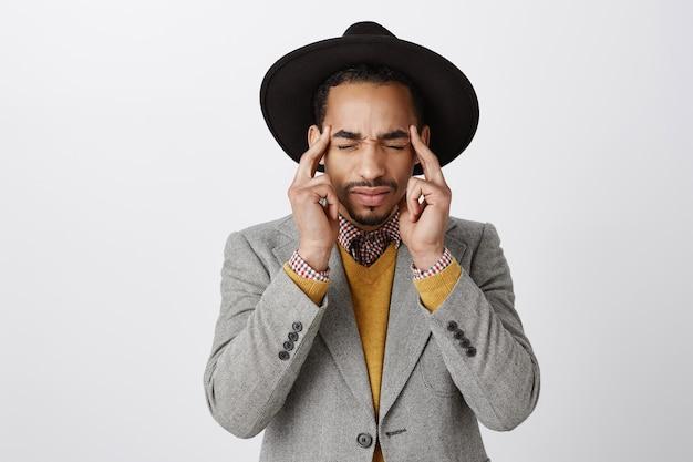 Close-up van duizelige afro-amerikaanse man, hoofd aanraken en ogen sluiten, klagen over hoofdpijn, migraine hebben