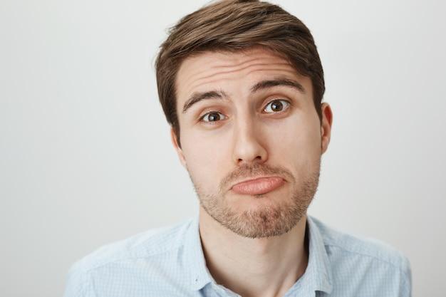 Close-up van dwaze en schattige jonge man pruilen, smeken om gunst
