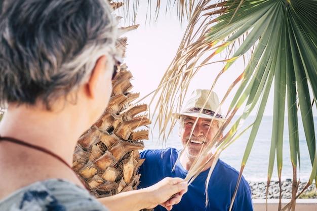 Close-up van een 70-jarige man die lacht onder een palmboom en verstoppertje speelt. vakantie, leuk concept