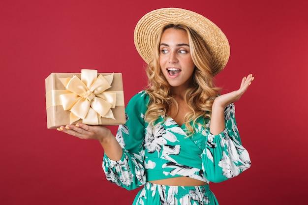 Close-up van een aantrekkelijke, gelukkige jonge blonde vrouw met een zomerjurk en een strohoed die geïsoleerd over een roze muur staat en de huidige doos toont