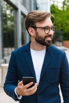 Close up van een aantrekkelijke glimlachende jonge bebaarde man met jasje met behulp van mobiele telefoon terwijl hij buiten in de stad staat