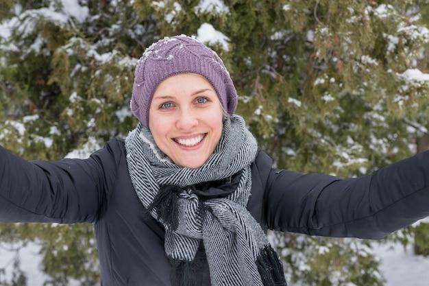 Close-up van een aantrekkelijke glimlachende vrouw die camera bekijkt