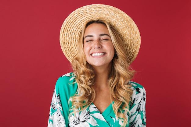 Close-up van een aantrekkelijke jonge blonde vrouw met een zomerjurk en een strohoed die geïsoleerd over een roze muur staat, lachend