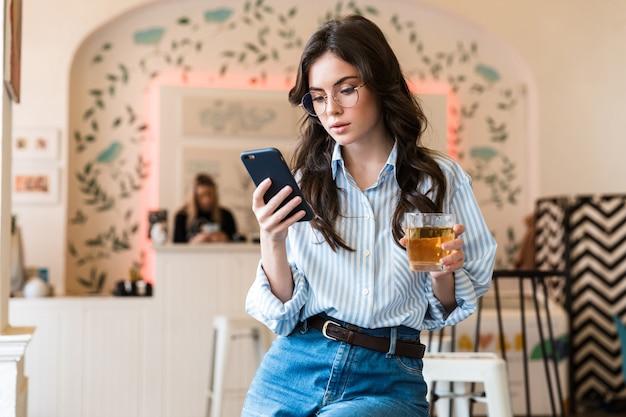 Close-up van een aantrekkelijke jonge brunette vrouw die een shirt draagt met een mobiele telefoon terwijl ze binnenshuis in het café zit