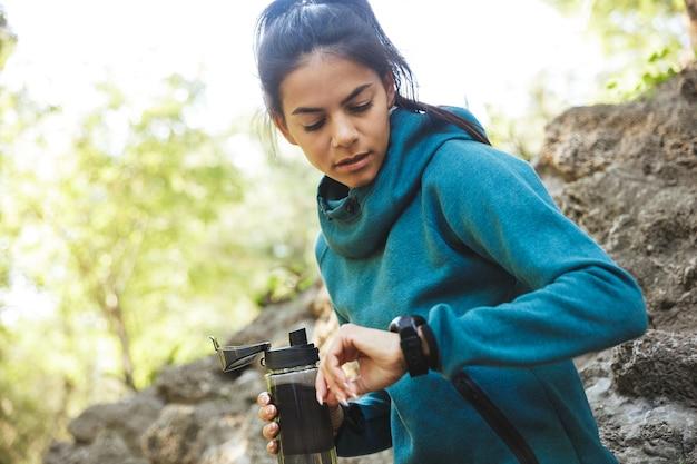 Close-up van een aantrekkelijke jonge fitness vrouw, gekleed in sportkleding buitenshuis oefenen, fles water te houden, kijkend naar haar horloge