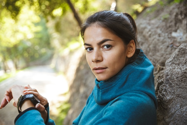 Close-up van een aantrekkelijke jonge fitness vrouw, gekleed in sportkleding buitenshuis oefenen met behulp van smartwatch
