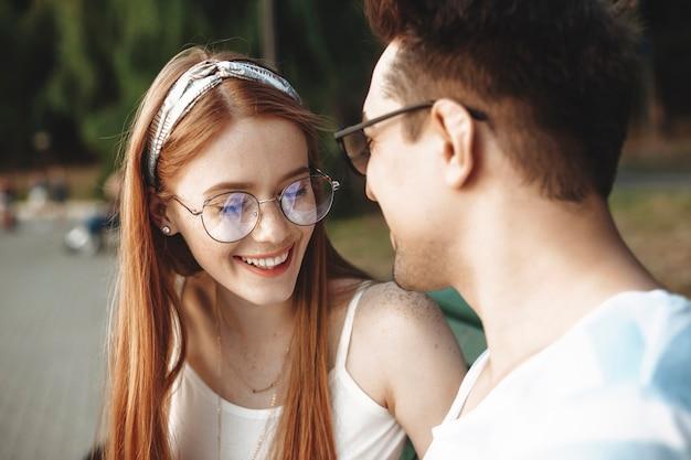 Close up van een aantrekkelijke jonge roodharige vrouw met sproeten lachen met gesloten ogen tijdens het daten met haar vriend buiten in het park.