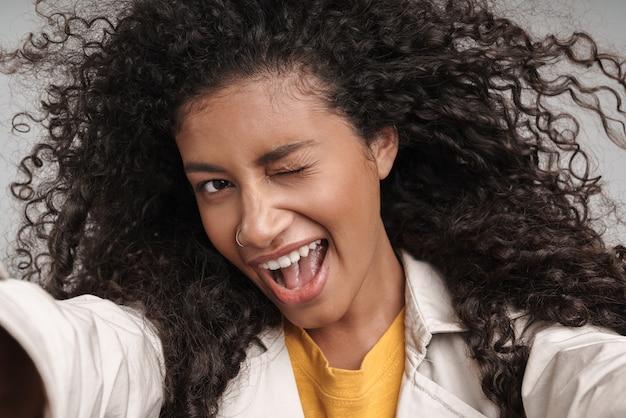 Close up van een aantrekkelijke lachende jonge afrikaanse vrouw met krullend haar, herfstjas dragen