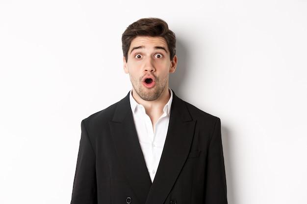 Close-up van een aantrekkelijke man in een zwart pak, verbaasd en onder de indruk van de advertentie, staande op een witte achtergrond