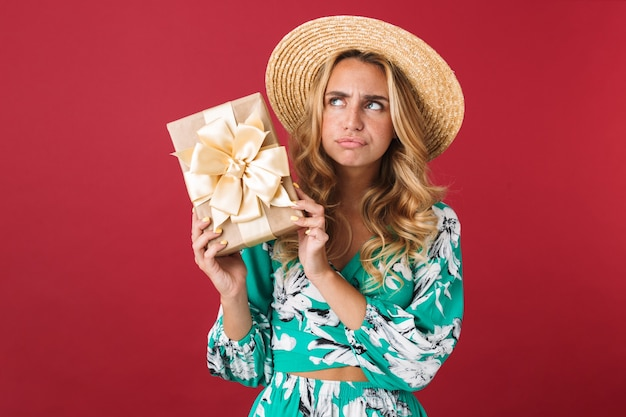 Close-up van een aantrekkelijke verwarde jonge blonde vrouw met een zomerjurk en een strohoed die geïsoleerd over een roze muur staat en de huidige doos toont