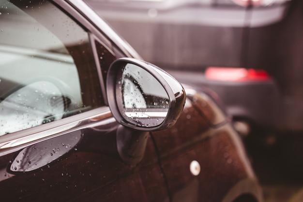 Close-up van een achteruitkijkspiegel van een bruine auto bedekt met regendruppels met een onscherpe achtergrond