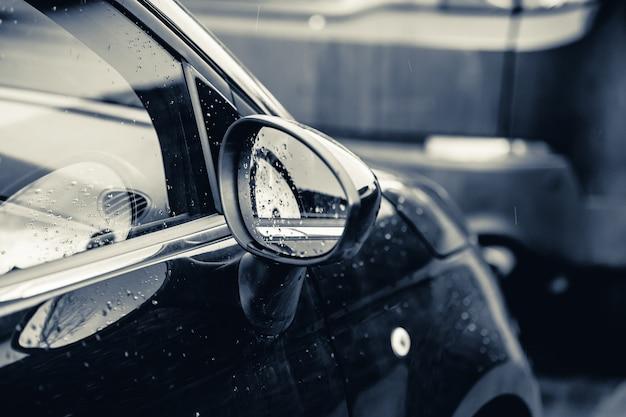Close-up van een achteruitkijkspiegel van een zwarte auto bedekt met regendruppels