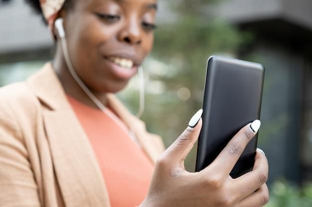 Close-up van een afrikaanse blogger die naar het scherm van haar mobiele telefoon kijkt terwijl ze hem buitenshuis gebruikt
