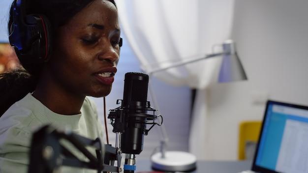 Close-up van een afrikaanse bloggervrouw die bij de microfoon spreekt tijdens podcast met behulp van professionele opnametechnologie in de thuisstudio