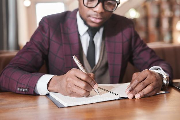 Close-up van een afrikaanse jonge zakenman die aan tafel zit en een lijst met plannen maakt in zijn notitieboekje