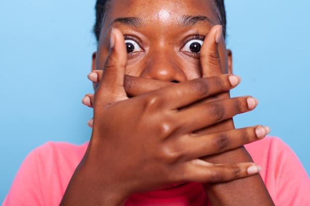 Close-up van een afro-amerikaanse jonge vrouw die de mond bedekt met geschokte gezichtsuitdrukkingen