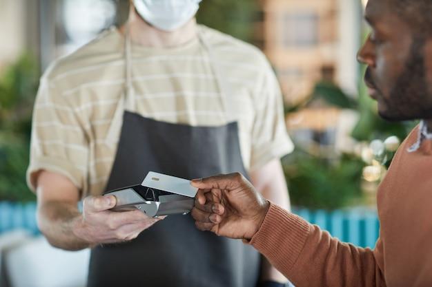 Close-up van een afro-amerikaanse man die betaalt met een mockup-creditcard in café of restaurant, kopieer ruimte
