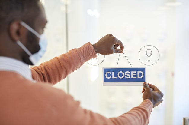 Close-up van een afro-amerikaanse man die een gesloten bord op de glazen deur van café hangt, covid-beperkingen concept, kopieer ruimte