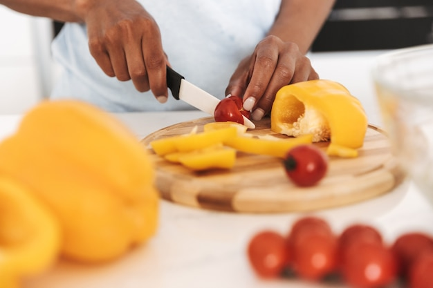 Close up van een afro amerikaanse vrouw hakken groenten