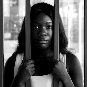 Close-up van een afro-amerikaanse vrouw met een droevige blik achter een ijzeren staaf, zwart-wit beeld