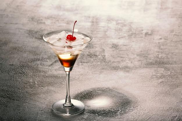 Close-up van een alcoholische cocktail met rum, ijs en versierd met rode kersen. conceptrecepten en mixologie.