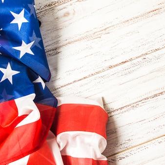 Close-up van een amerikaanse vlag van de vs met sterren en strepen op witte plank achtergrond