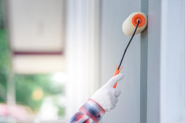 Close-up van een arbeider die de muren van het huis met de hand en verfroller schildert. grijze of cementkleurige verf