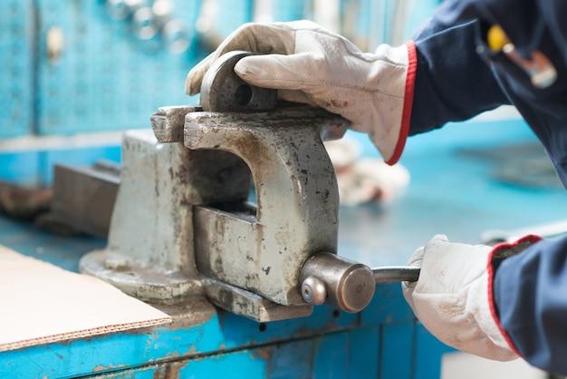 Close-up van een arbeider die een metaalplaat in een bankschroef beveiligt
