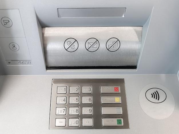 Close-up van een atm-toetsenbord en een compartiment voor het ontvangen en uitgeven van bankbiljetten.
