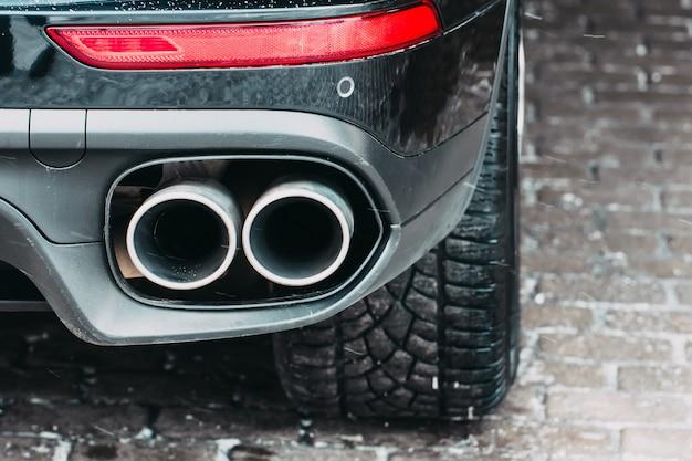 Close up van een auto dubbele uitlaatpijp parkeerlichten, remlichten en wielbanden.
