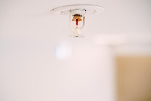 Close-up van een automatisch de sproeisysteem van de plafondbrand op een wit plafond